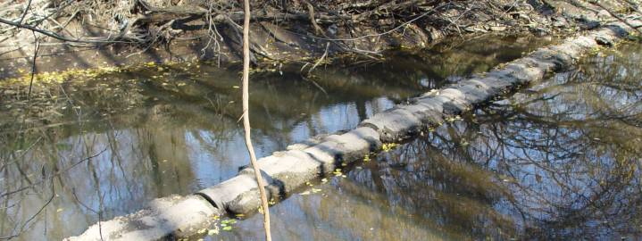 Exposed pipe in creek bed