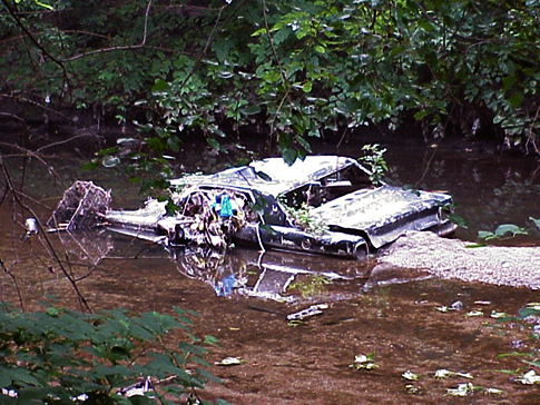 A car rests in a stream in the city's Northeast. Credit: Waterways Restoration Team,