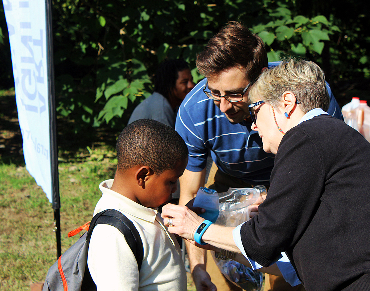 Commissioner Debra A. McCarty helps a West Philly Student put on a new button at 2016 rain garden ribbon cutting event. She became the first woman to lead the department. Credit: Brian Rademaekers