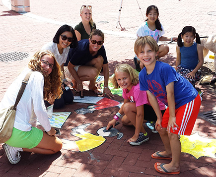 Juliette Kang, a 4th grader from Germantown Friends who took one of the top prizes, installs her art at Penn's Landing with family and friends.