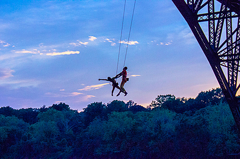 Performers from INVISIBLE RIVER 2014 hang suspended from the Strawberry Mansion Bridge. Credit: INVISIBLE RIVER.